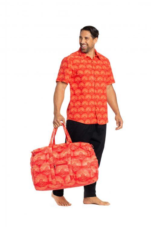 Male model wearing Hula Shirt S-S in Fiery Red/Musk Melon Kalihilehua, carrying a Laulea Bag