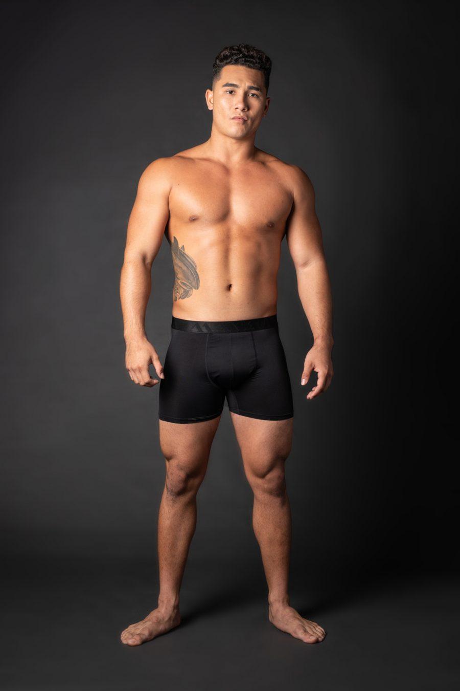 Male model wearing Uwila Midway Briefs in Black Solid Pattern - Front View