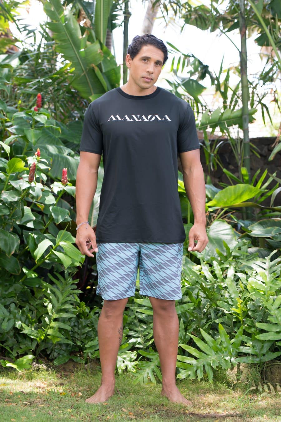Male model wearing Manaola Logo T-Shirt in Solid Black with White Writing - Front View