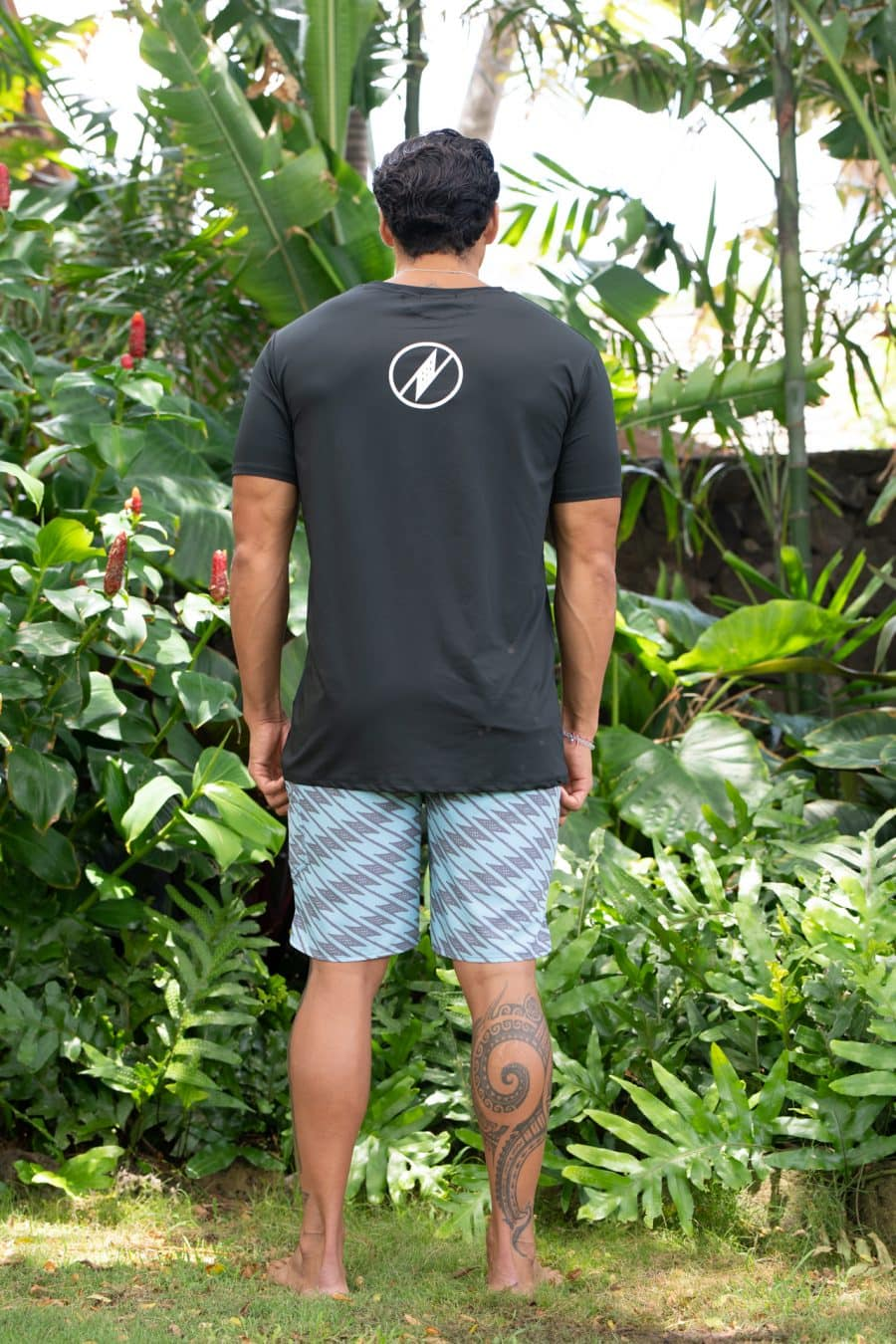 Male model wearing Manaola Logo T-Shirt in Solid Black with White Writing - Back View