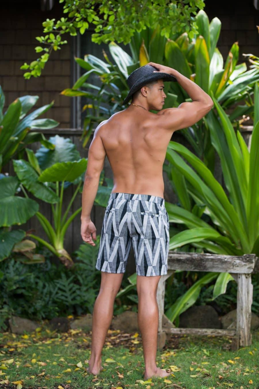 Male model wearing Keola Shorts in Black Windchime Kanaloa Pattern - Back View