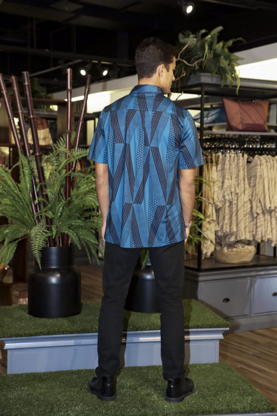 Male model wearing Golf Aloha Button in Blue Sapphire Black Kanaloa Pattern - Back View
