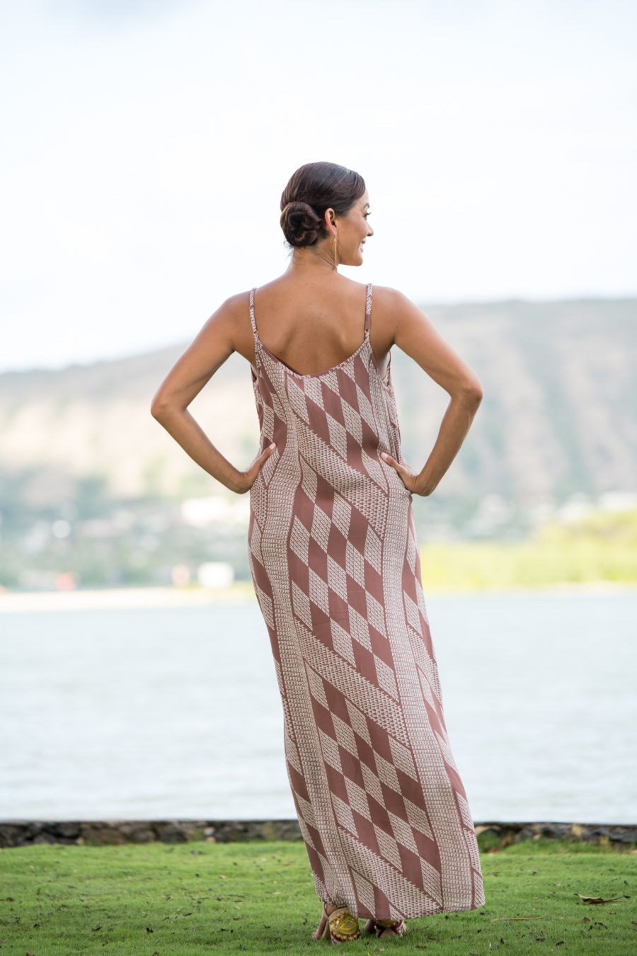 Model wearing Uluniu Maxi Dress in Fired Brick White Kamehameha Pattern - Back View