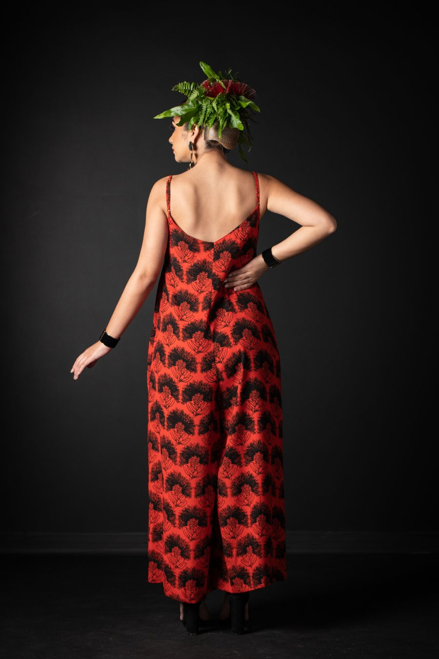 Model wearing LANIHAU JUMPSUIT in Firey Red Black Kalihilehua Pattern - Back View