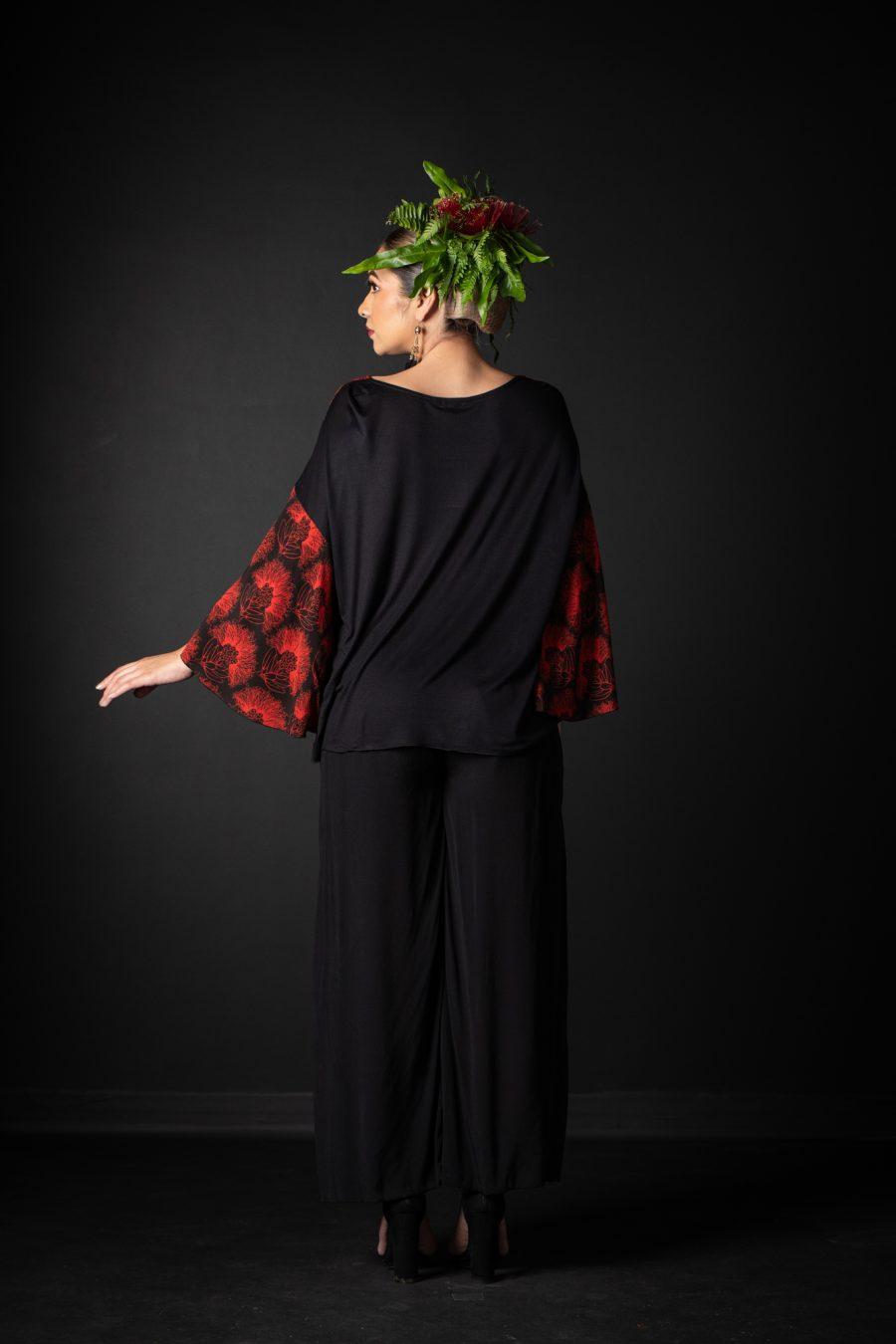Model wearing Hoolaulea Top in Firey Red Black Kaleilehua Pattern - Back View