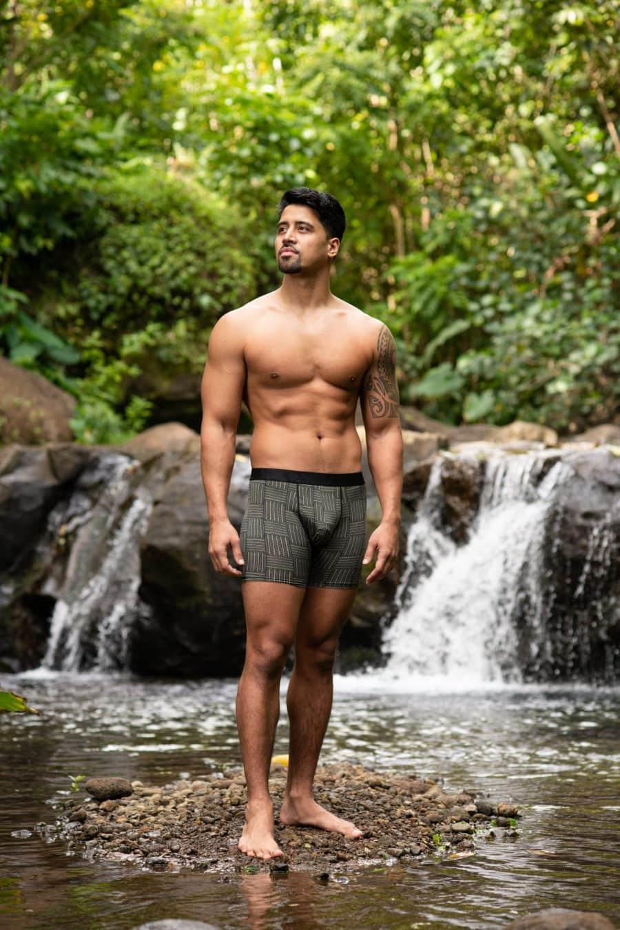 Male model wearing Manaola Boxer Trunk in Martini Olive-Jet Black Ulana Pattern - Front View