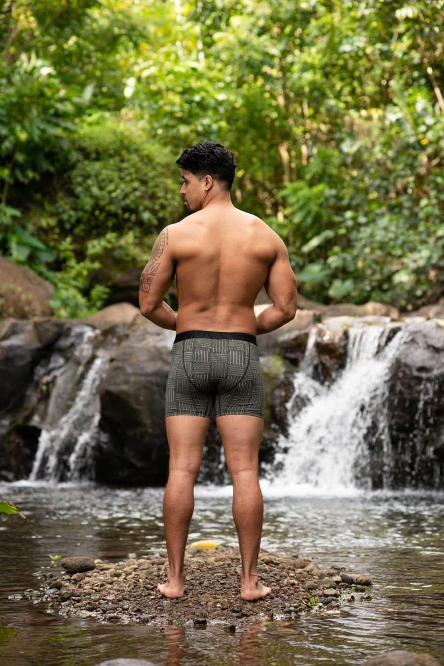 Male model wearing Manaola Boxer Trunk in Martini Olive-Jet Black Ulana Pattern - Back View