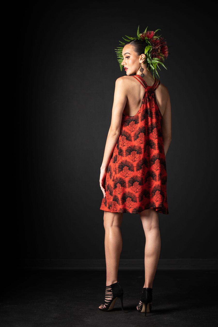Model wearing Kaimanahila Short Dress in Firey Black-Red Kalihilehua Pattern - Back View