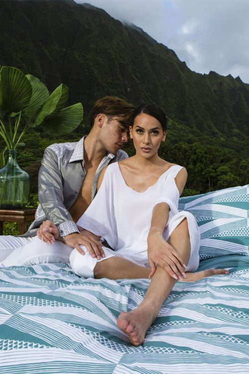Male and Female Model sitting on Manaola Duvet King Set in Seafoam Kanaloa Pattern