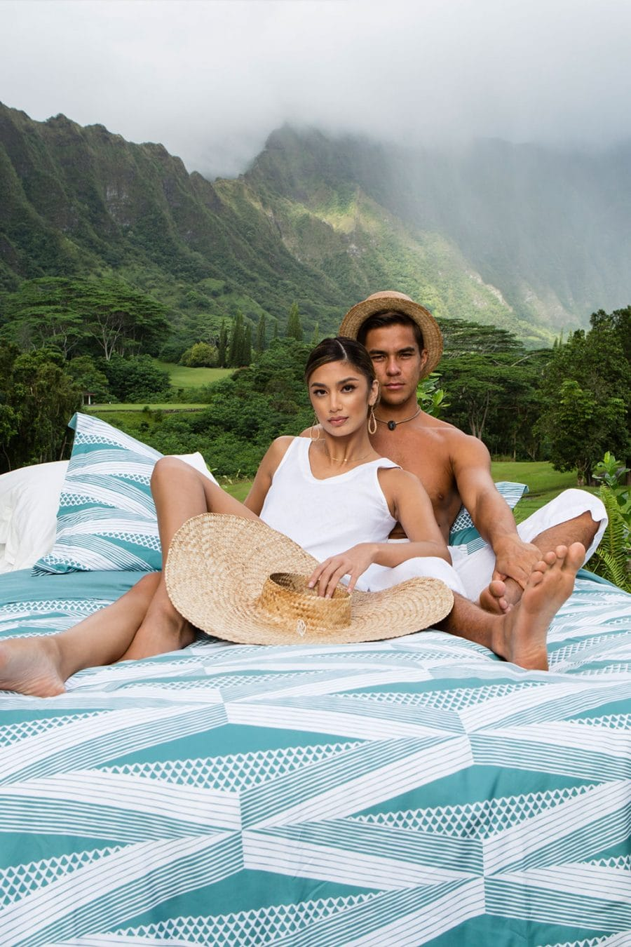 Male and Female Model sitting on Manaola Duvet Queen Set in Seafoam Kanaloa Pattern