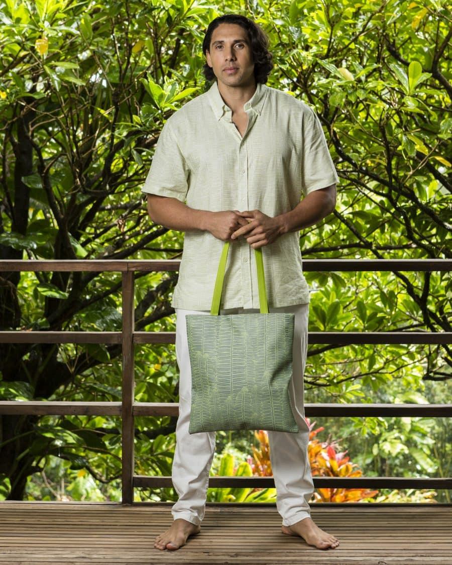 Male model holding Puke Tote in Lily Pad Margarita Kupukupu pattern