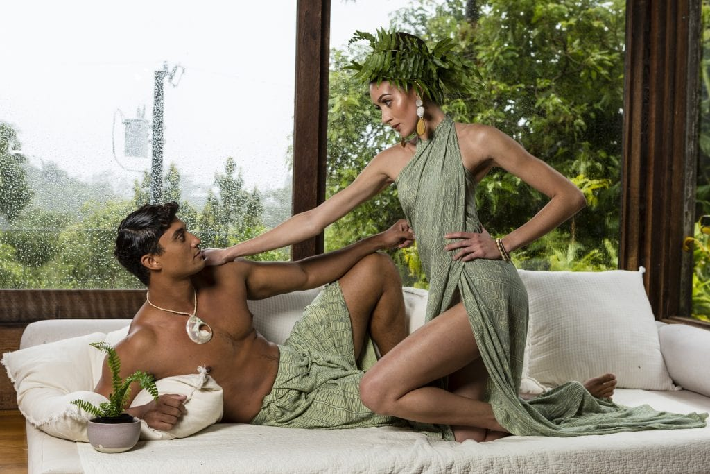Male and Female Model Looking at Each Other on White Couch Wearing Kupu Collection Clothing