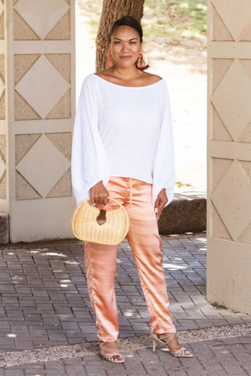 Female model wearing Uluhala Joggers in Nanaka Pattern and Coral Sands-Peach Whip Color - Front View