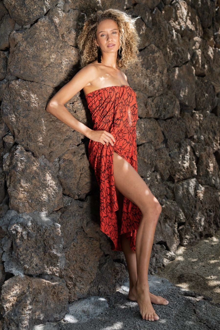 Female model wearing a Pareo in Kapualiko Pattern and Firey Red/Black - Side View