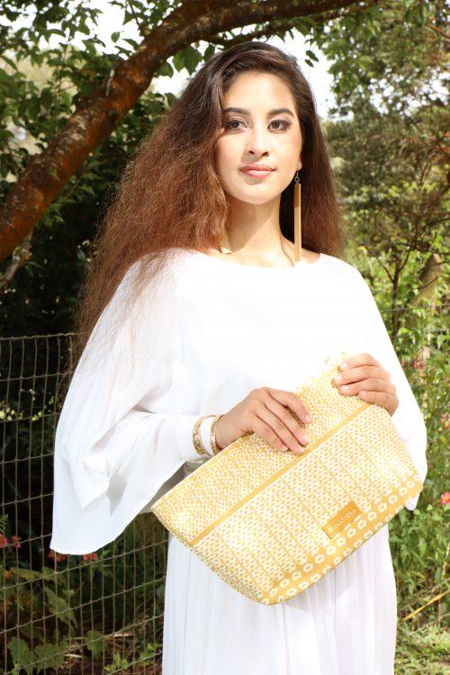 Female model holding Hapuna Clutch in Ako'Akoa'a Pattern in Rise Color
