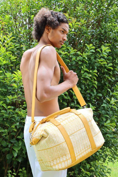 Male model holding Kaapuni Mini Duffel in Ako'Akoa'a Pattern in Rise Color