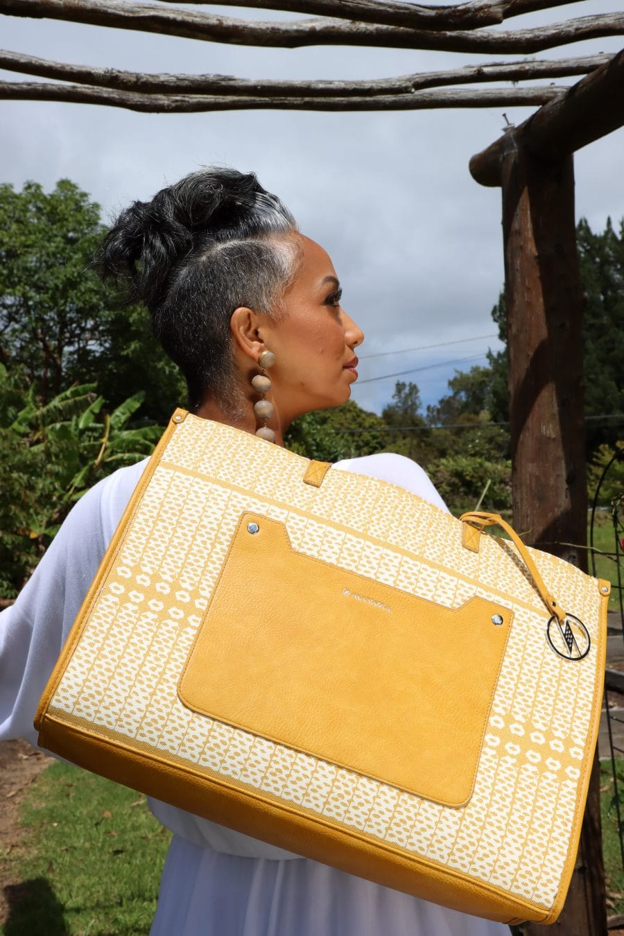 Female model holding Kaulu Tote in Ako'Akoa'a Pattern in Rise Color