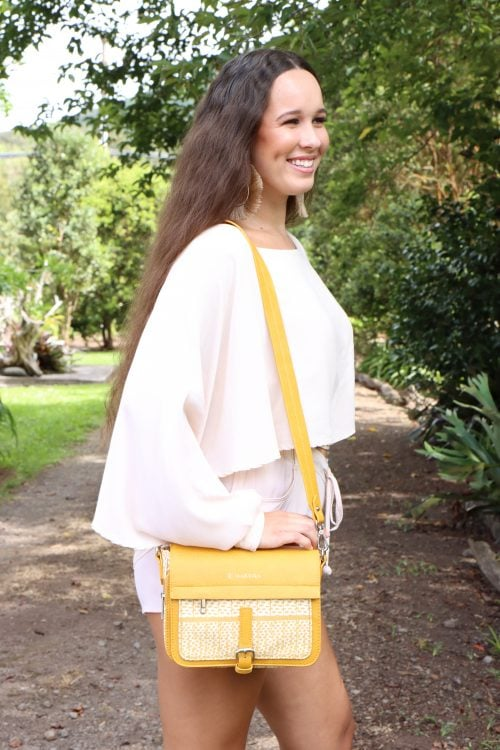 Female Model holding the Puaniu Crossbody in Ako'Ako'a in Rise Color - Side View