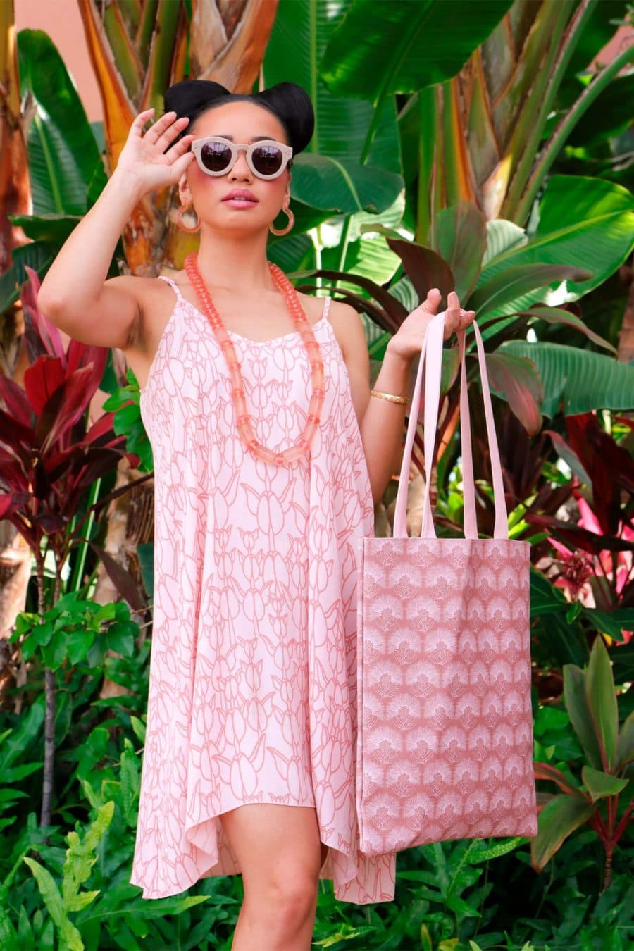 Female Model holding a Puke Tote in a Kalihilehua Pattern and Lotus-Ash Rose Color