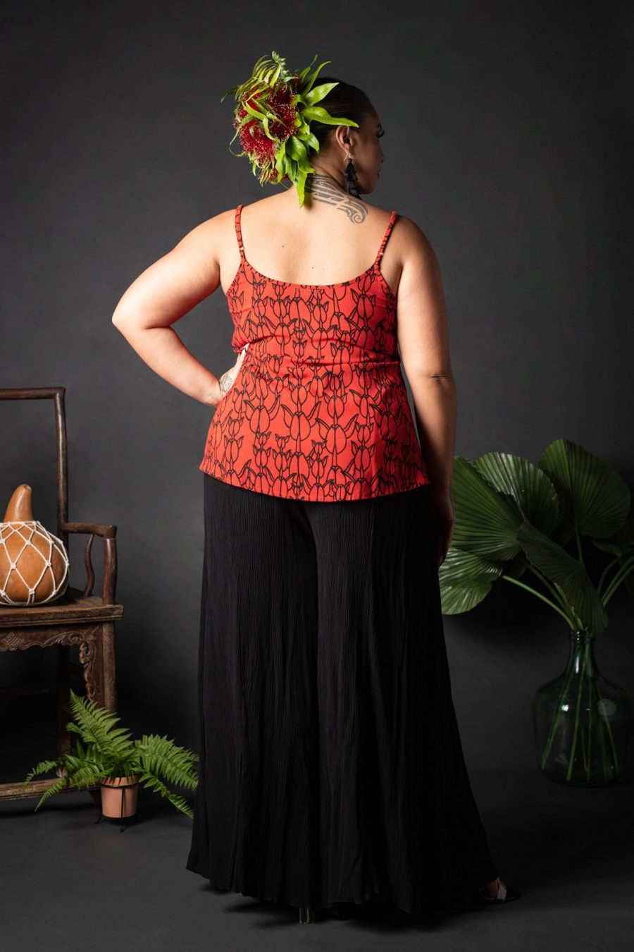 Female model wearing a Manaola Top 6 in a Kapualiko pattern and Fiery Red and Black Color - Back View