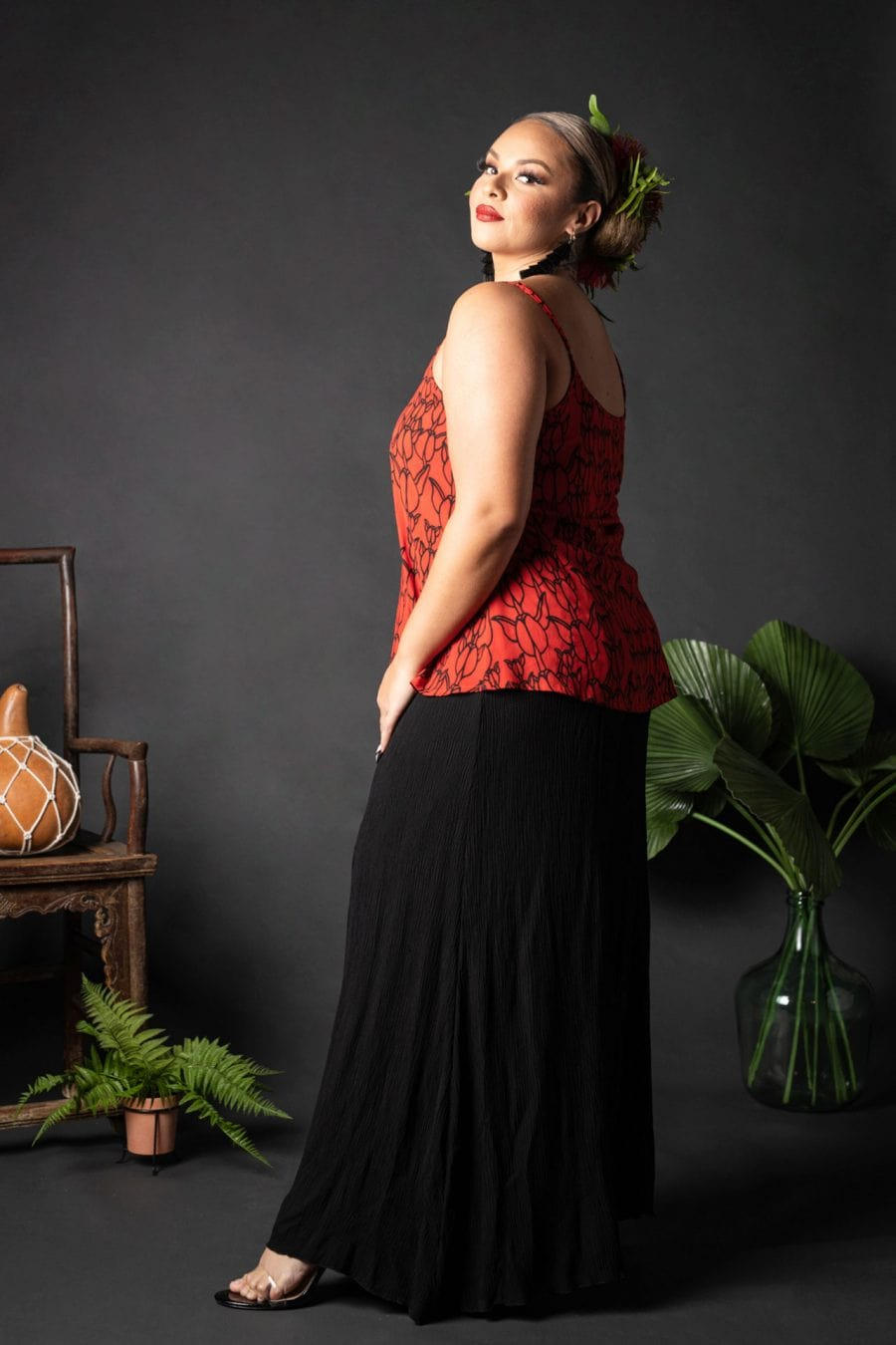 Female model wearing a Manaola Top 6 in a Kapualiko pattern and Fiery Red and Black Color - Side View